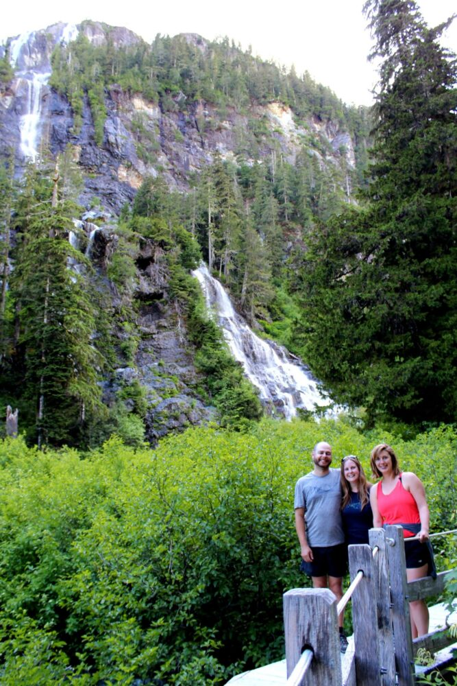 Three hikers on bridge viewpoint of Della Falls