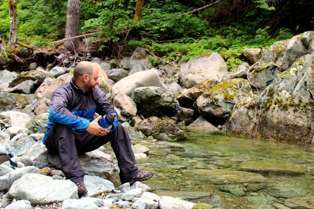 JR sat on a rock next to Drinkwater Creek, looking at the turquoise water