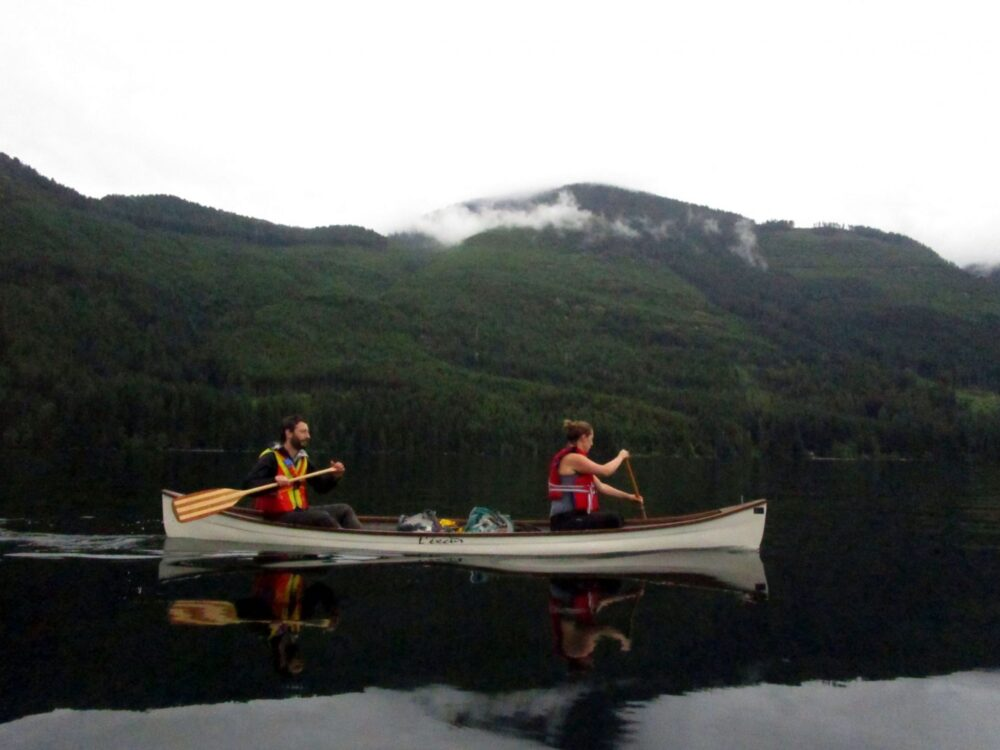 Two canoeists on Great Central Lake - the water is calm and mirrorlike