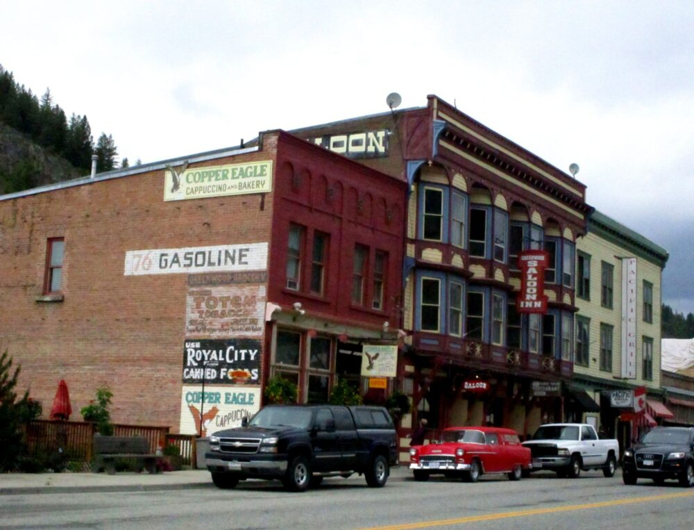 Old fashioned buildings with advertising on the side, with cars parked outside - Greenwood, BC