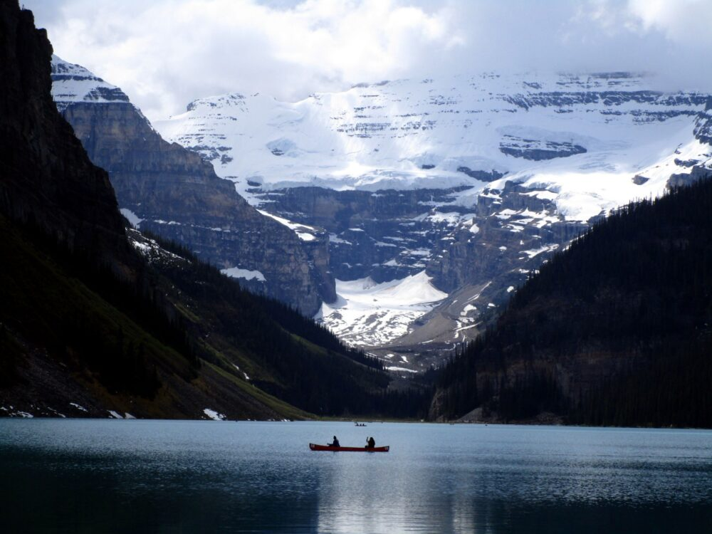 Canoeists paddling on mountain lake with snow capped peaks behind