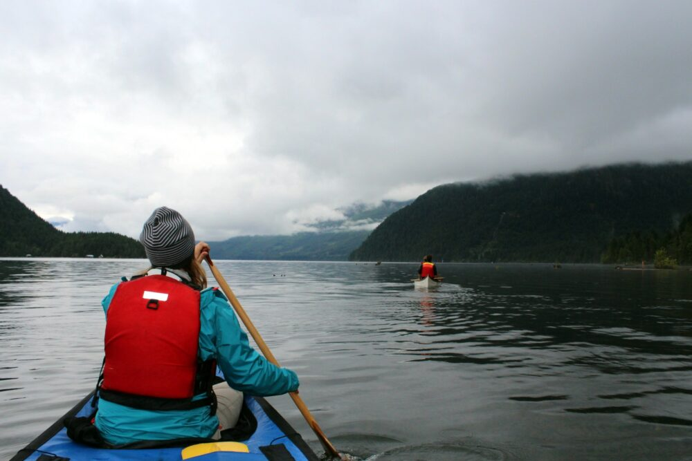 Canoe paddling under low clouds on Great Central Lake, heading to the Della Falls trail