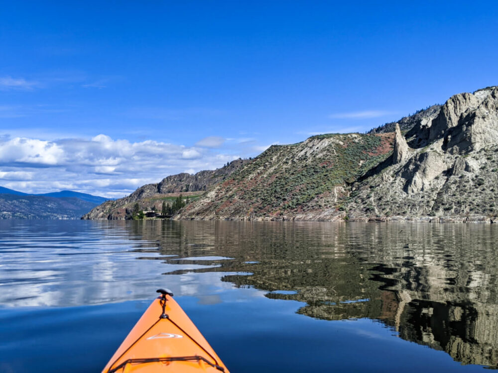 Kayak view of calm Okanagan Lake with rugged, dry landscape. There are a number of distinctively shaped hoodoos on the right (columns of weathered rocks)