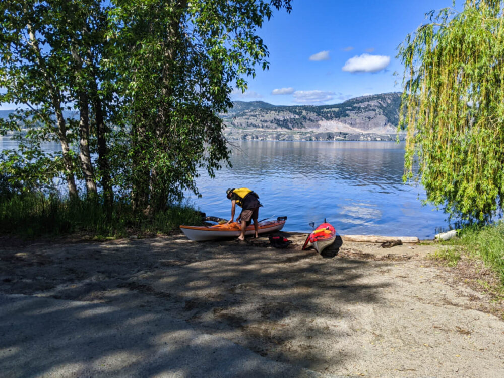 Orange and red kayaks sat on shore next to the lake at Indian Rock boat launch. JR is standing over orange kayak and putting items in storage compartments