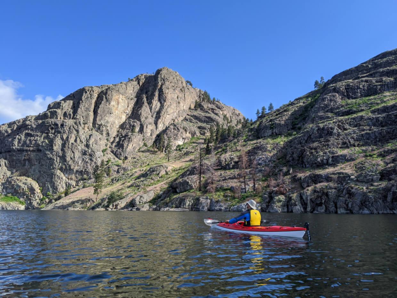JR sits in red kayak on calm Okanagan Lake, paddling close to the rugged shore of Okanagan Lake