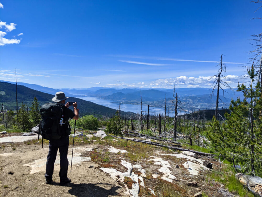 JR stands on rock taking photo of view of Okanagan Lake below surrounded by mountainous terrain, with some burnt trees in foreground