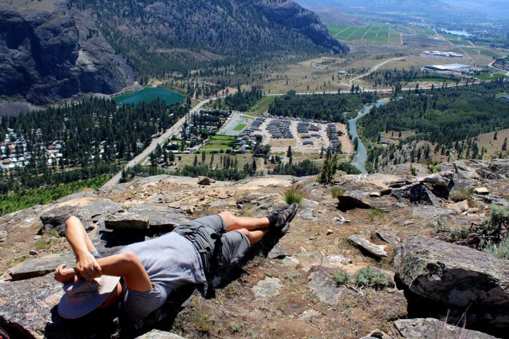 JR lying on rocks at the top of McIntyre Bluff, Okanagan Valley with vineyards and roads beyond