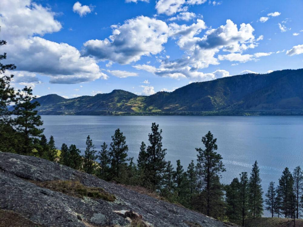 Looking across rocky landscape towards Okanagan Lake below, backdropped by hilly green terrain