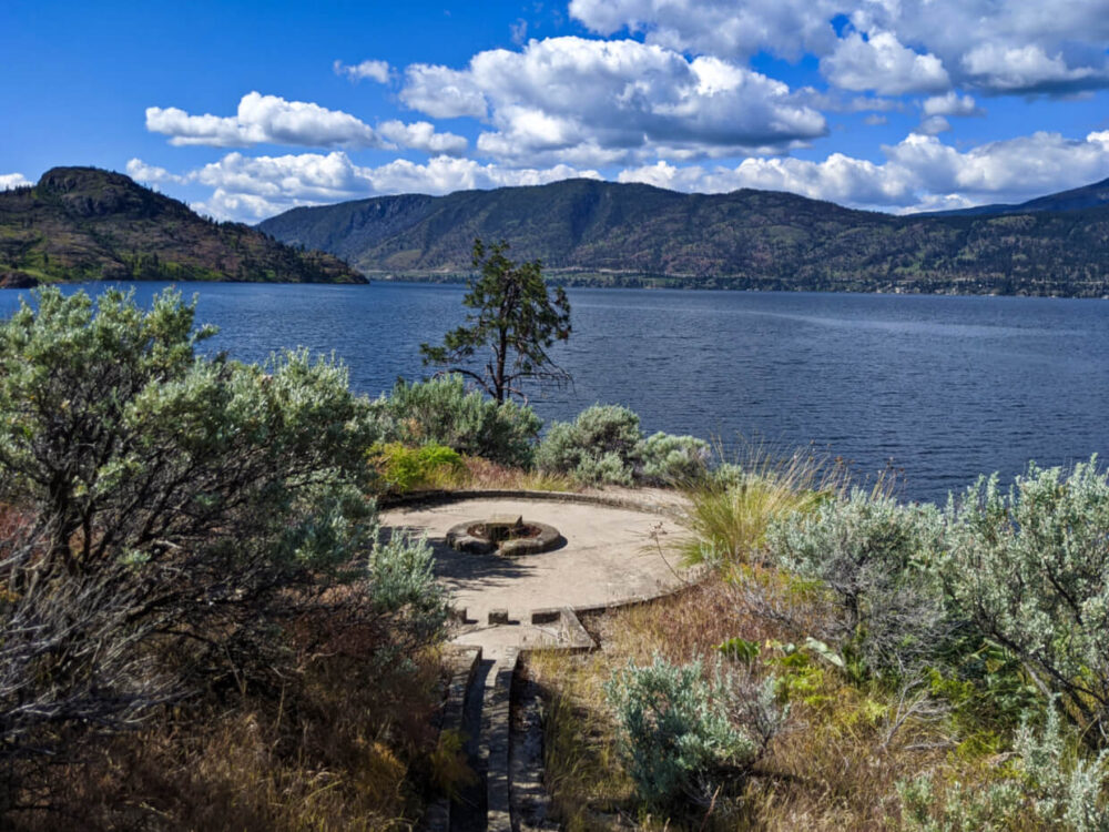 Concrete miniature golf course hole surrounded by shrub bushes on Rattlesnake Island, with views of Okanagan Lake and mountainous terrain behind