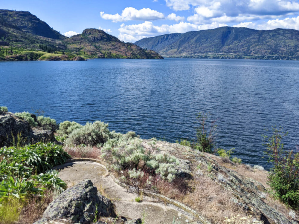 Concrete miniature golf hole surrounded by shrubby landscape, backdropped by Okanagan Lake and rugged landscape of Okanagan Mountain Park