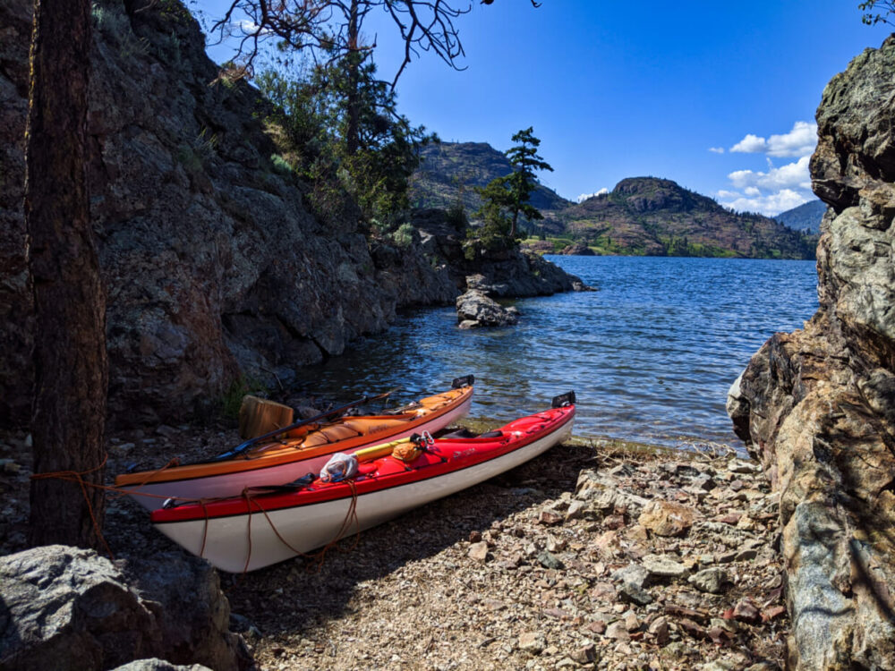 Orange and red kayaks sitting on rock shore in narrow cove on Rattlesnake Island