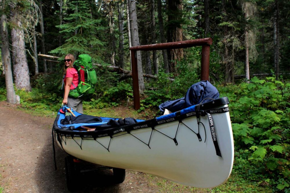 portaging a canoe on the bowron lakes canoe circuit, british columbia