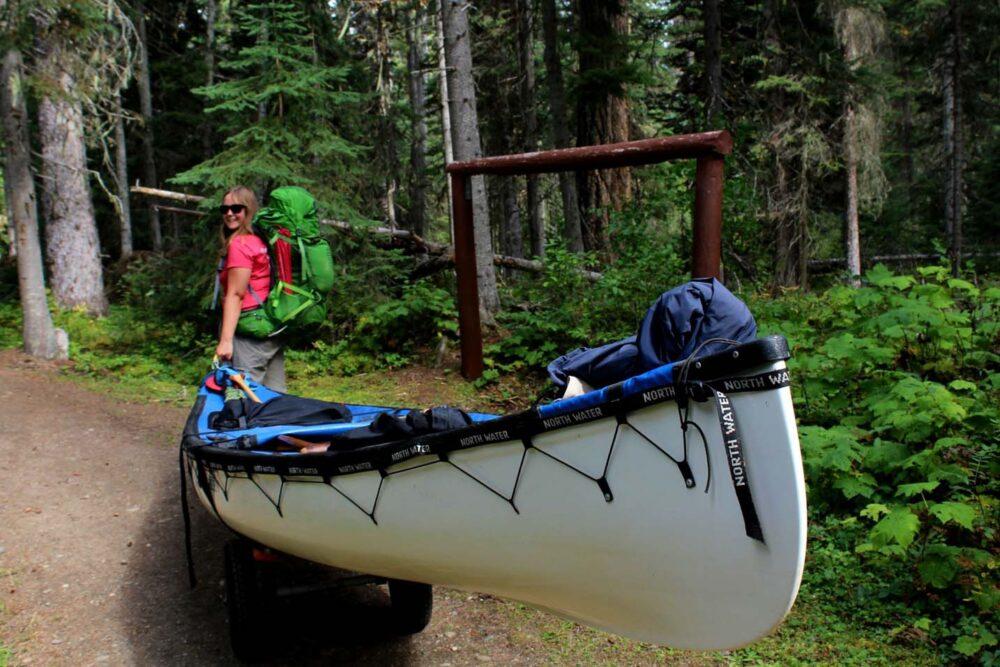 Gemma pulling white canoe on wheels along trail on the west side of Bowron Lakes Canoe Circuit