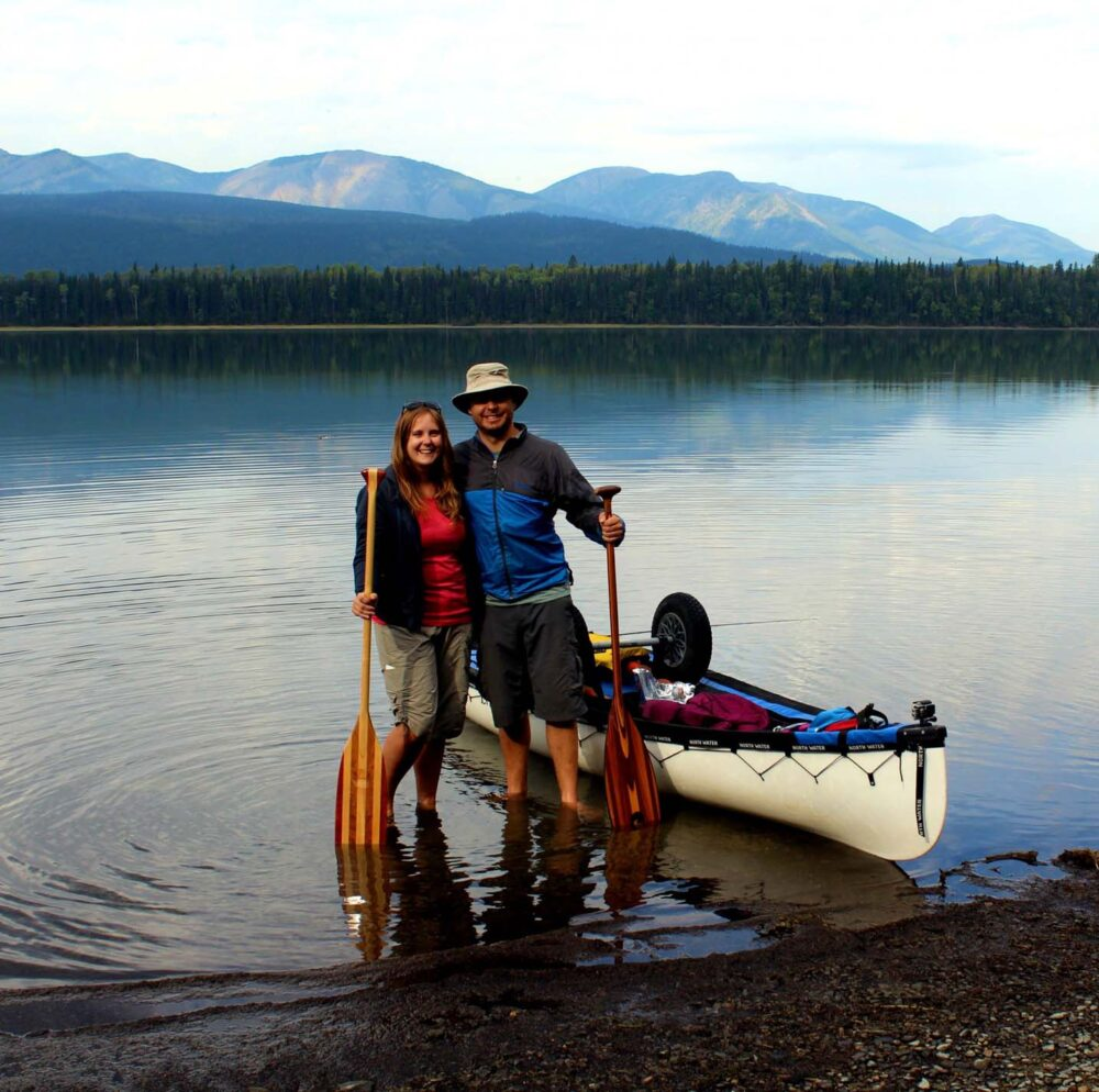 Gemma and JR standing with canoe paddles next to canoe on calm lake