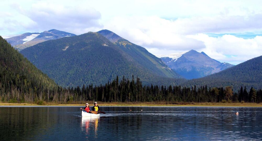 JR and Gemma paddling on Bowron Lakes Canoe Circuit, one of the best canoe trips in Canada