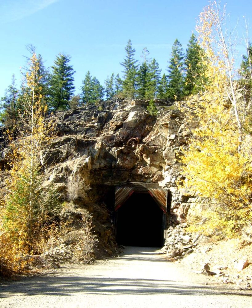 Dark tunnel built into rock with wooden structure surroundings at Myra Canyon