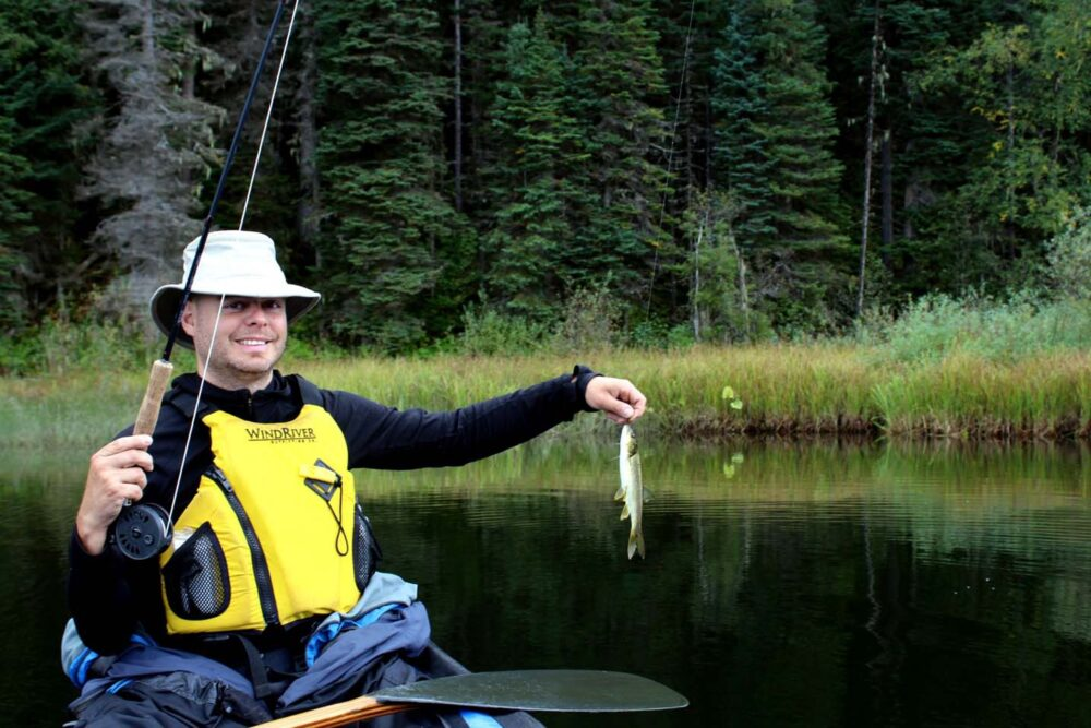 JR in  canoe on Bowron River with fishing rod and holding small caught fish
