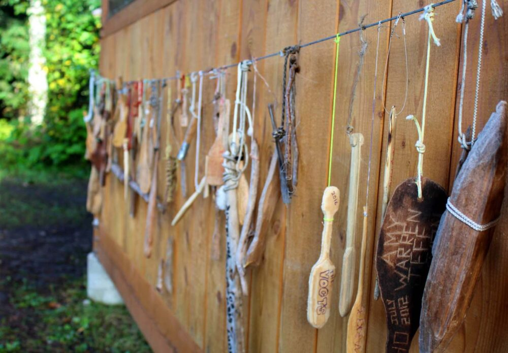 Close up of carved wooden mini canoe paddles hanging outside a wooden shelter on the Bowron Lakes Canoe Circuit