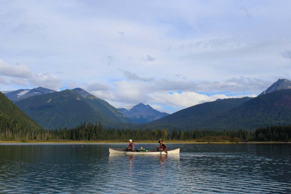 White canoe with two paddlers on calm lake with mountain background