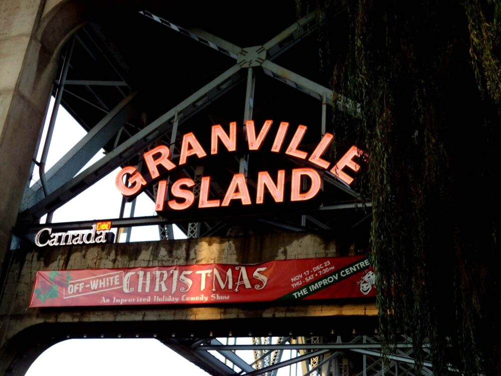 Entrance signs for Granville Island, under a busy city bridge