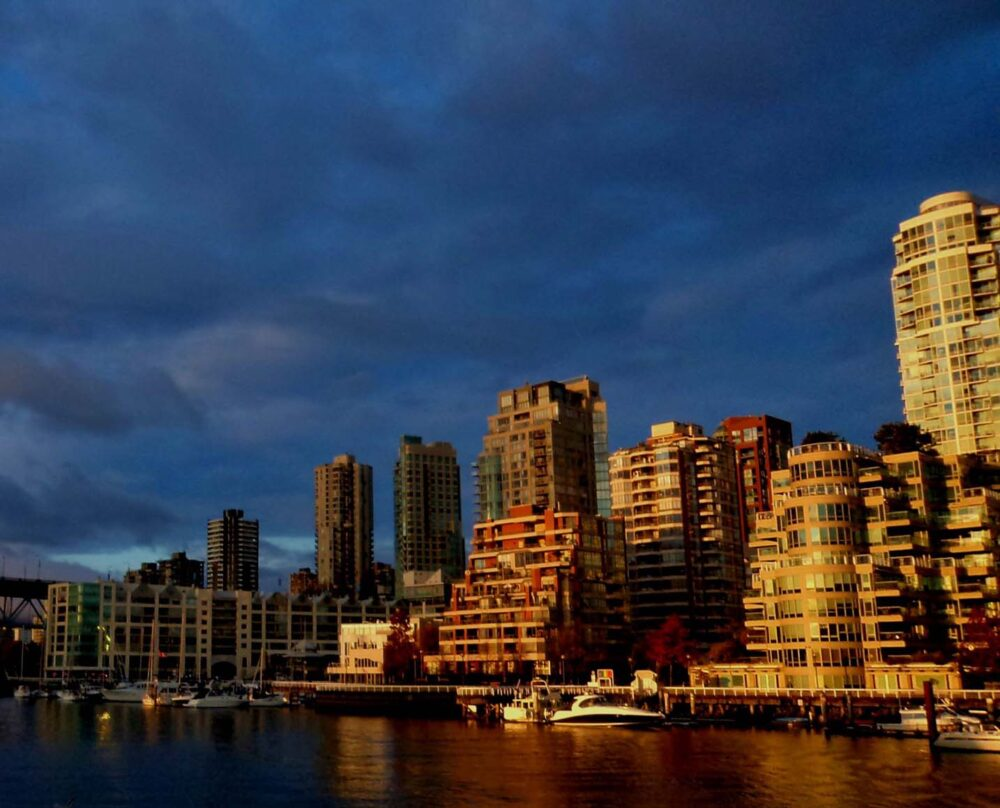 High rise buildings along False Creek highlighted at sunset