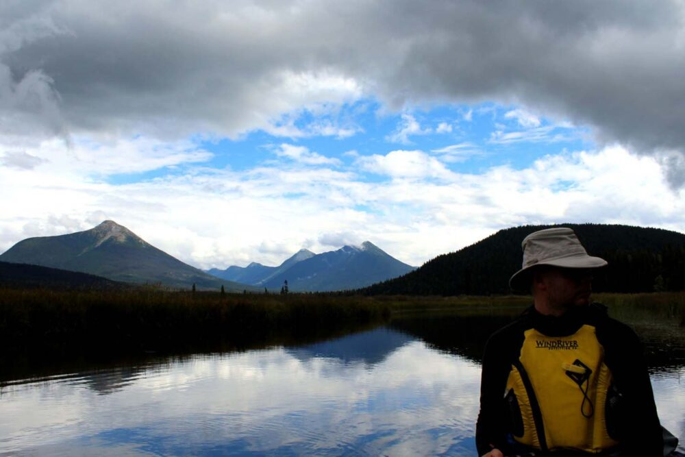JR sat wearing yellow PFD in canoe on calm river with mountainous backdrop
