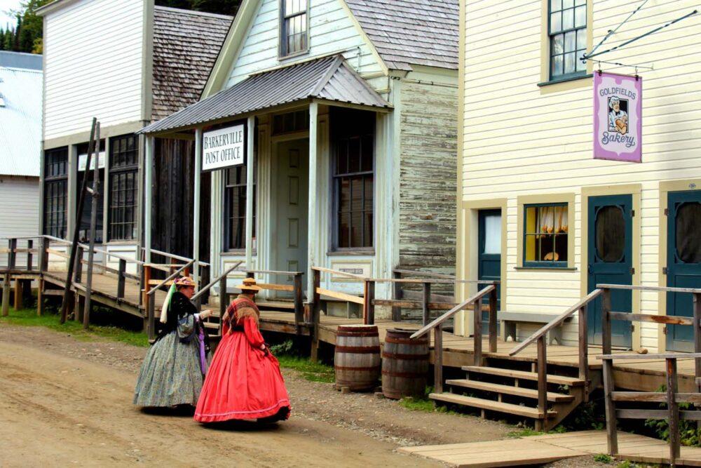 Two Barkerville actors walk towards Goldfields Bakery on Main Street
