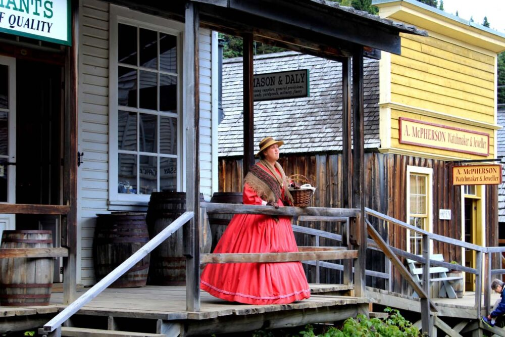 Barkerville character actor with pink dress on wooden walkway