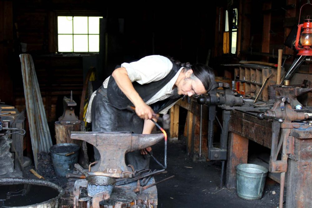 A blacksmith works at an anvil at Barkerville's forge