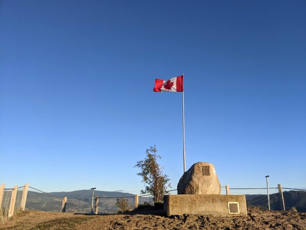 View of rock on concrete base. with Canadian flag in background at Giant's Head Mountain summit