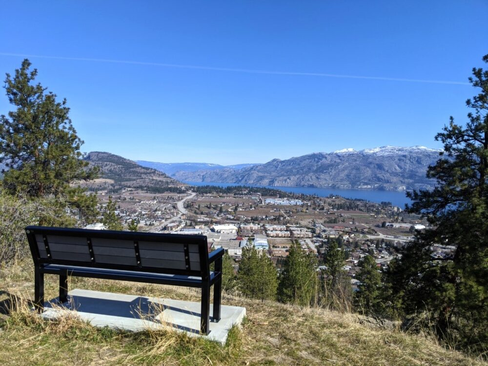 Bench on Giant's Head Mountain hike looking out to views of Summerland with lake and mountains behind