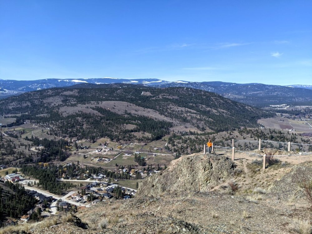 Summit views towards the industrial side of Summerland, with rolling hills, snow topped mountains and Gemma standing at a fenced viewpoint