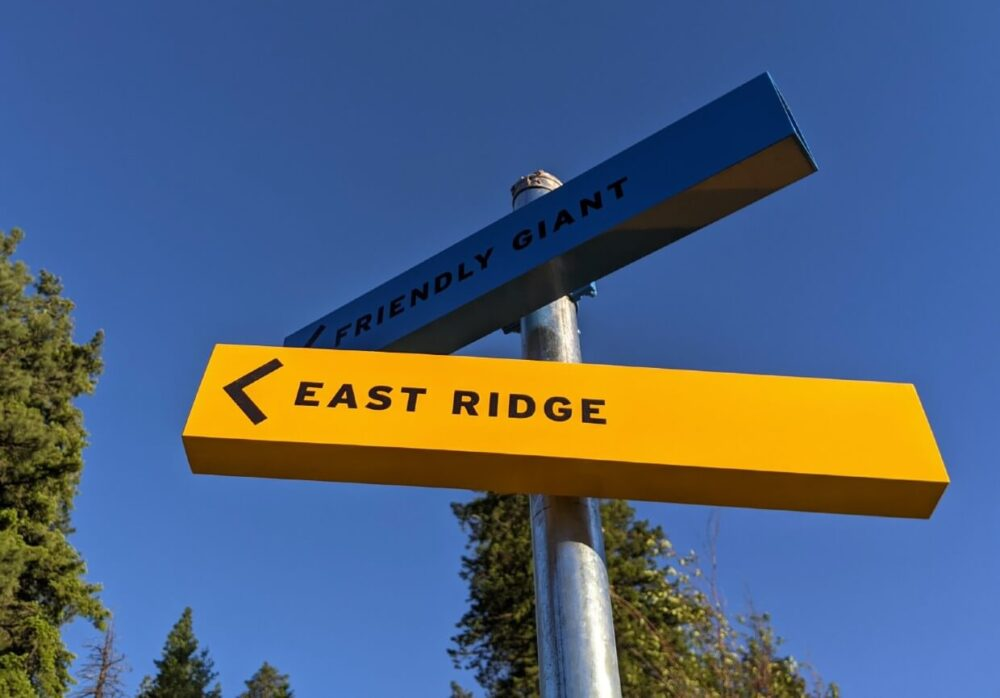 Close up of two hiking trail signs on Giant's Head Mountain - East Ridge on yellow rectangle and Friendly Giant on blue rectangle