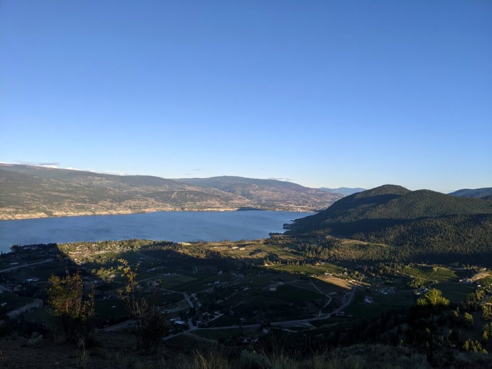 Sunset view of southern views from Giant's Head Mountain with vineyards and houses below, with Okanagan Lake in background and hills beyond