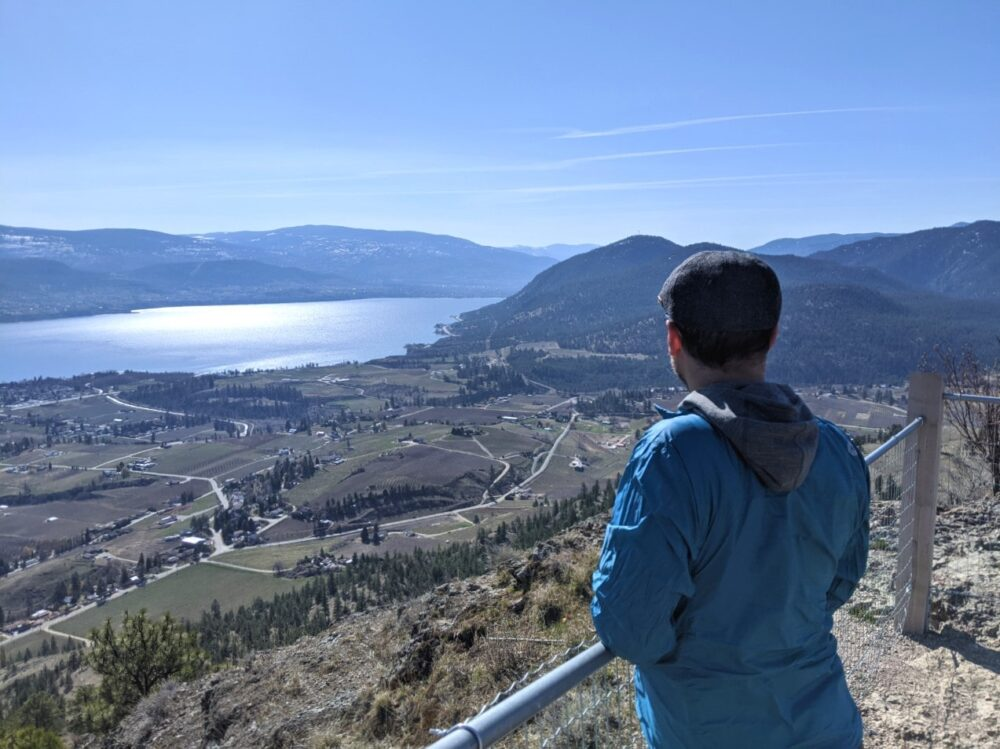 JR standing behind fence, looking out over Okanagan Lake, Highway 97 from the top of Giant's Head Mountain