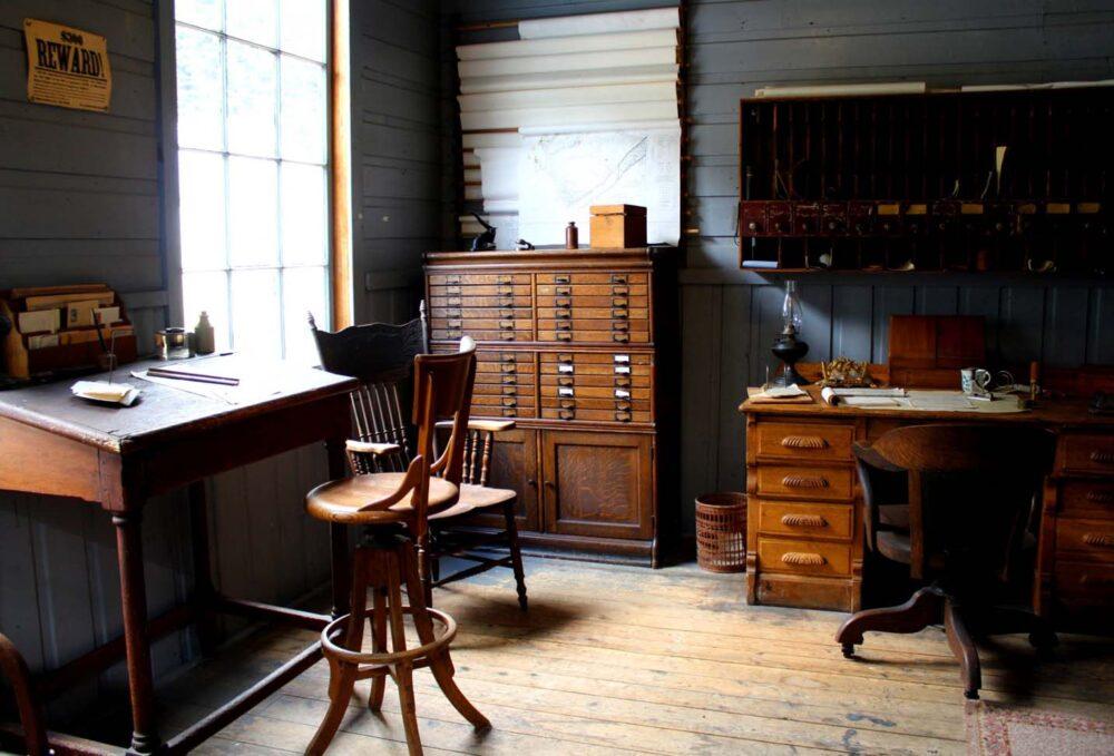 Desks and cabinets set against blue wooden walls