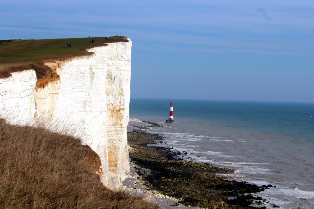 Beachy Head chalk cliff with striped lighthouse below