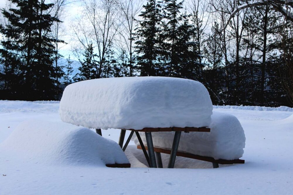 Picnic table with huge amount of snow on surface and bench