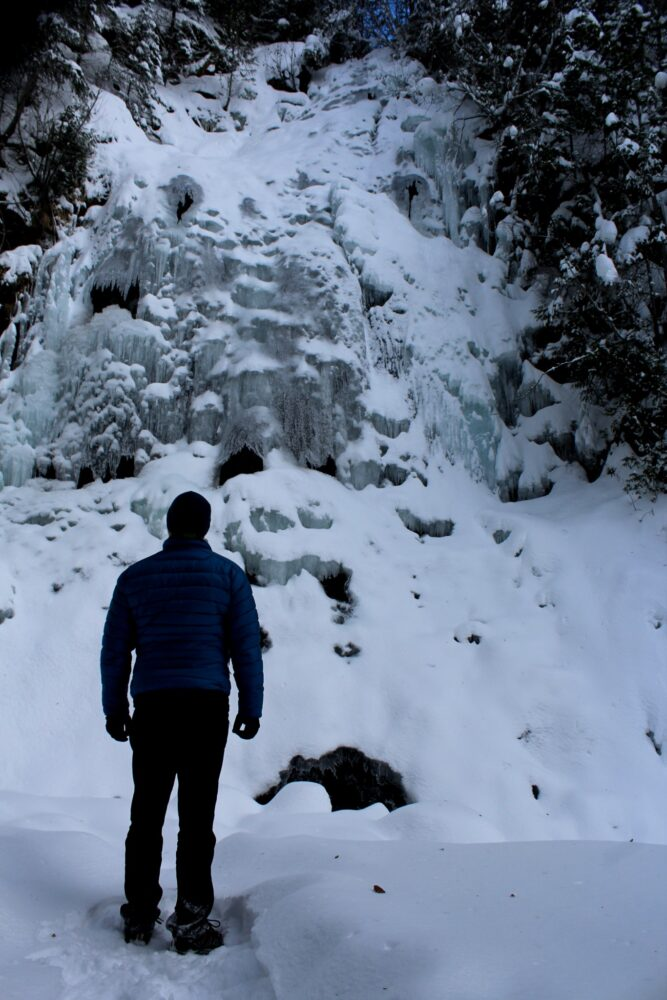 JR looking at frozen waterfall covered with snow