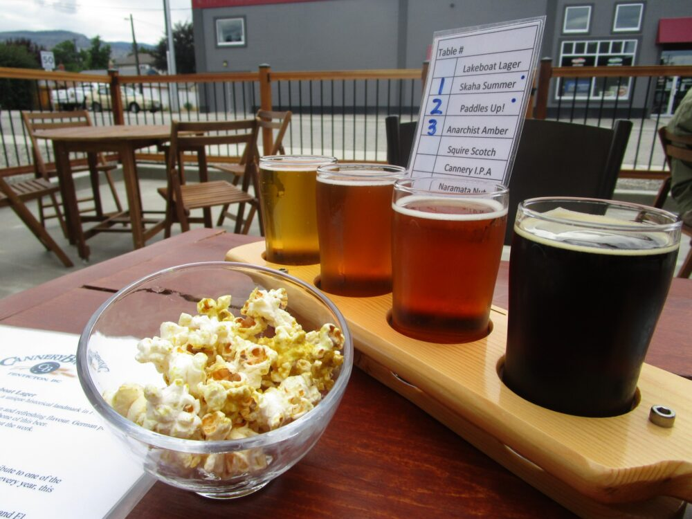 Cannery Brewing tasting flight with four beers and a bowl of complimentary popcorn, on outdoor patio table