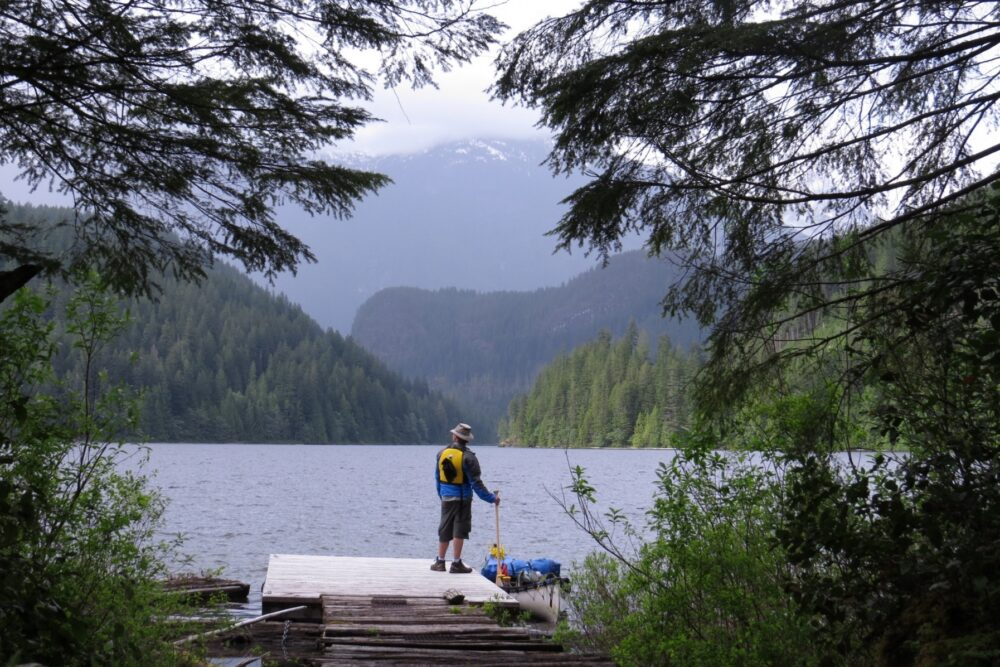 Distant view of JR standing on canoe dock in front of lake, with layers of mountains behind