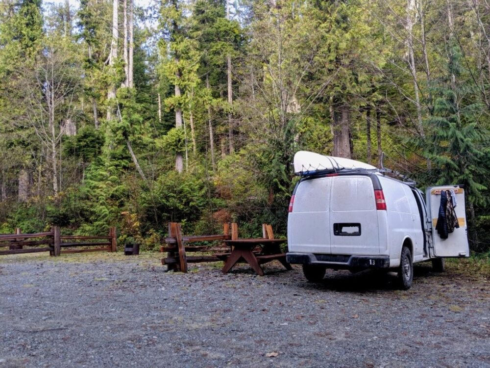 White van parked inbetween wooden fences, next to picnic table with background of trees