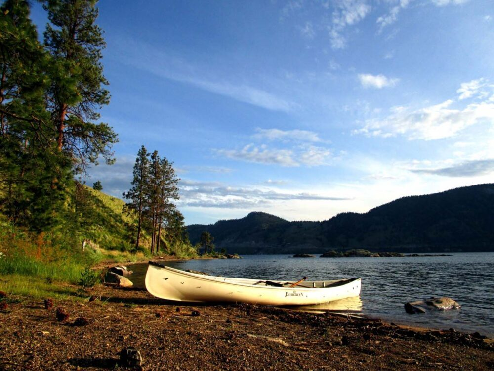 White canoe sitting on shore at sunset, with calm lake and mountainous backdrop