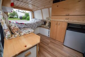 Interior view of our GMC Savana van conversion, with laminate flooring, fridge, fitted storage, panelled ceiling and more. offtracktravel.ca