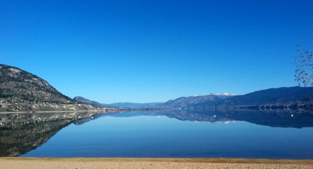 The crystal clear waters of Okanagan Lake, lined with golden sands