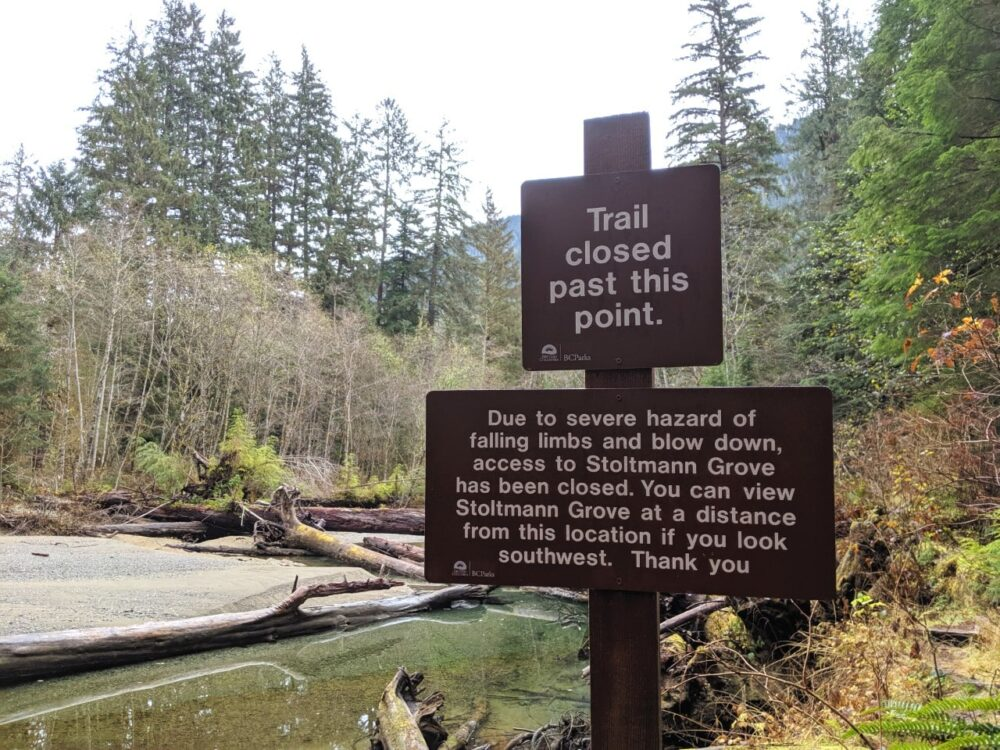Two brown signs in front of a river stating that the trail is closed beyond this point