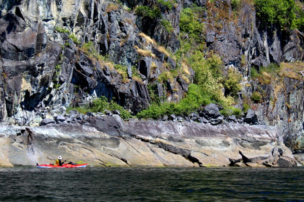 Rocky shoreline in Desolation Sound, BC. Kayaker paddling past