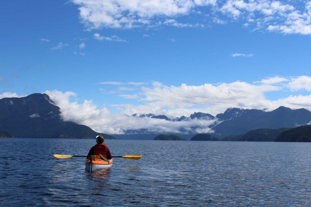 Kayaker with mountain range and ocean behind, classic Desolation Sound views