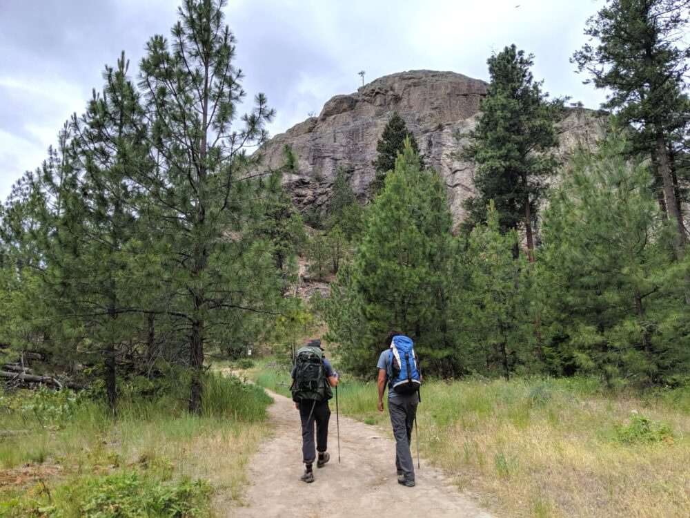 Two climbers with backpacks walk towards the bluffs