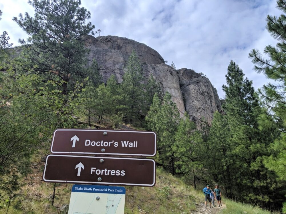 Brown signs with Doctor's Wall and Fortress marked, leading to the Skaha Bluffs